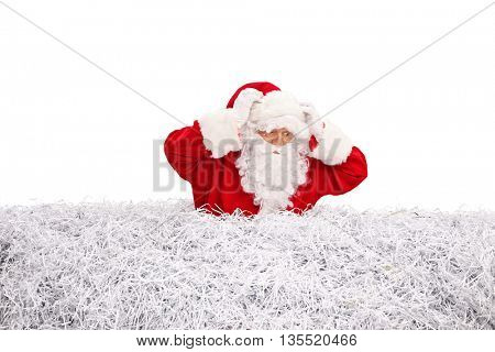 Confused Santa Claus searching for something in a pile of shredded paper isolated on white background