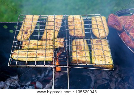Fresh healthy green zucchini on a barbecue grill over charcoal. Grilled zucchini slices. Vegetarian, Mediterranean cuisine.