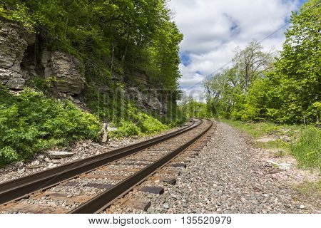 A single railroad track curving around a hill.