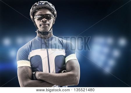 Composite image of cyclist crossing his arms against spotlight