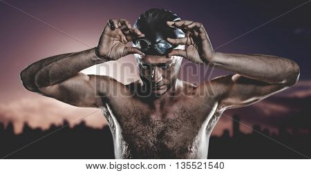 Swimmer holding swimming goggles against picture of a city by sunrise