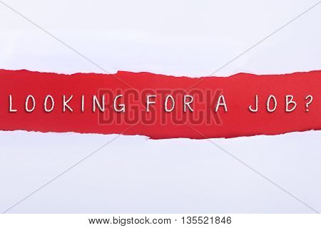 Torn paper with a LOOKING FOR A JOB word on red background.