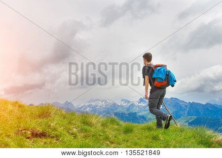 Boy Walking In The Mountains With His Stick In The Meadows