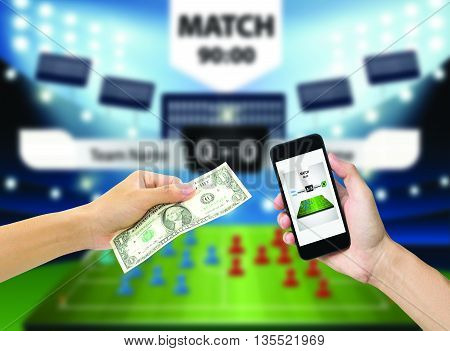 Hand holding mobile phone view live soccer euro game on mobile phone and Hand holding money with football field background.