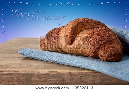 croissant on blue napkin on wood and good morning written and heart frame