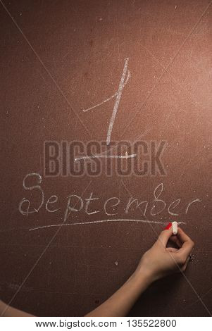 Chalkboard with September 1 written in white chalk1st of September. Hand writing on a blackboard.