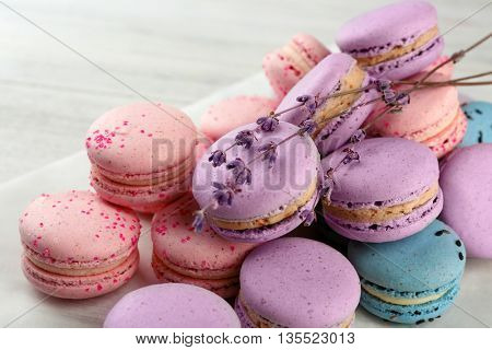 Tasty macaroons with twigs on wooden table