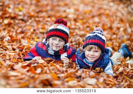 Two little friends boys lying in autumn leaves in colorful clothing. Happy siblings kids having fun in autumn forest or park on warm fall day. With hats and scarfs