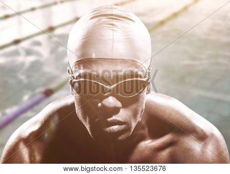 Swimmer ready to dive against view of a swimming pool