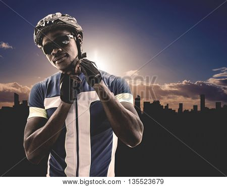 Composite image of athletic man putting his cycling helmet against cityscape