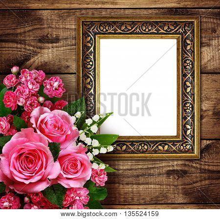 Pink flowers arrangement and a frame for photo or text on brown wooden background. Roses lily of the valley hawthorn flowers.