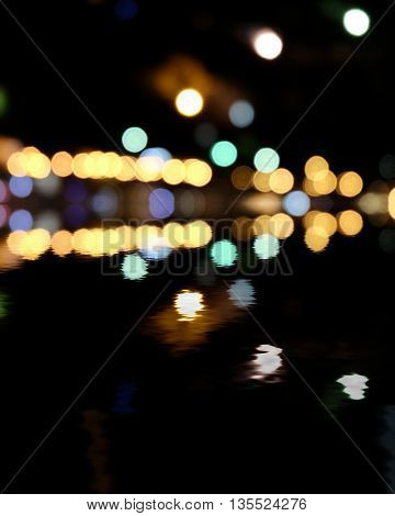 Yellow and green spots on black. Blurred city at night, bokeh background. Reflection of colorful lights in water and a lot of copyspace