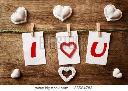 cord with three paper and clothespins on wood with i love you written and chalk heart