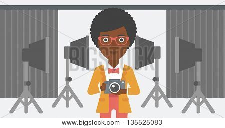 An african-american woman holding a camera on the background of photo studio with lighting equipment vector flat design illustration. Horizontal layout.