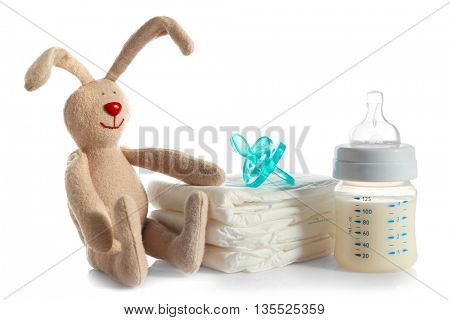 Baby bottle with milk, pile of diapers and rabbit toy isolated on white