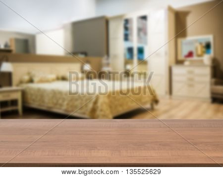 Wooden board empty table in front of blurred background. Perspective dark wood over blur in modern comfortable bedroom with beige bed. Mock up for display or montage your products