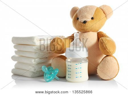 Baby bottle with milk, pile of diapers and teddy bear isolated on white