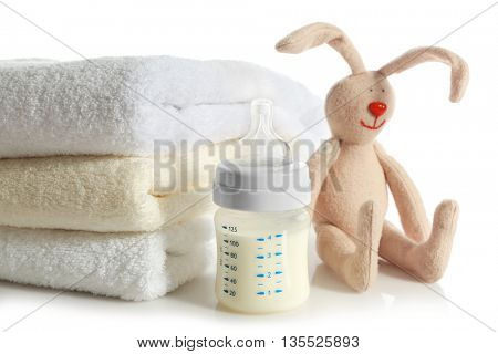 Baby bottle with milk, pile of soft towels and rabbit toy isolated on white
