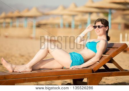 Woman Relaxing On Wooden Lounger