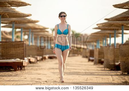 Young Woman Walking On Sunny Sand Beach