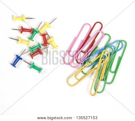 Multicolored paperclips and pin pisolated on white background