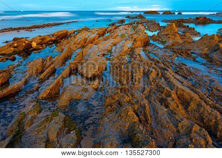 Twilight Ocean Coast With Ribbed Stratiform Rock.