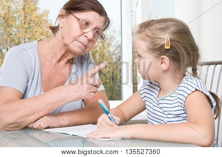 Strict elderly women learn to read her granddaughter.