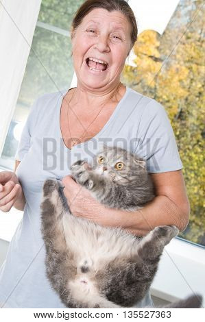 Laughing elderly woman trying to hold on the naughty cat hands.