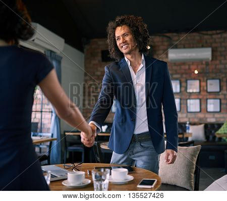 Businessman shaking hands with partner in cafe