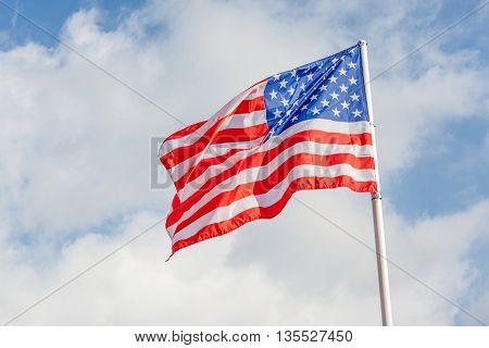 American flag waving against cloudy blue sky focus on star of waving flag.