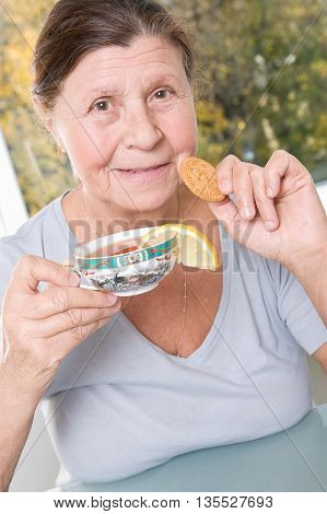 Elderly woman drinking tea with cookies. Studio photography in bright tones.