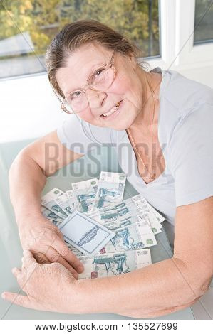 Happy middle-aged woman raking the table stack of Russian money and passbook.