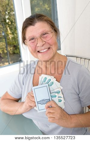 Happy elderly woman presses the breast stack of Russian money and passbook.