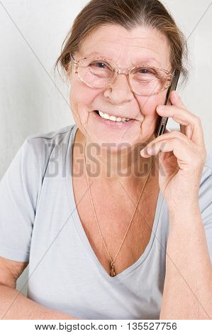 Happy elderly woman talking on a cell phone.