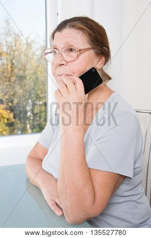 Thoughtful elderly woman holding a mobile phone.