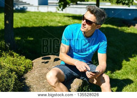 athlete sitting with bottle of water and mobile phone on the stone in the park