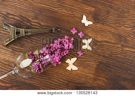 Wineglass with lilacs and decorations on the wooden background