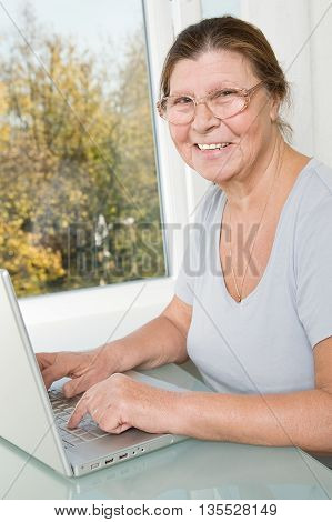 Happy elderly woman working at a computer.