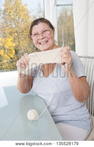 Elderly woman showing her tied a sock. Studio photography. Light background.