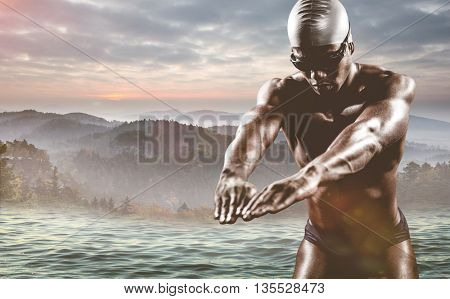 Swimmer ready to dive against trees and mountain range against cloudy sky