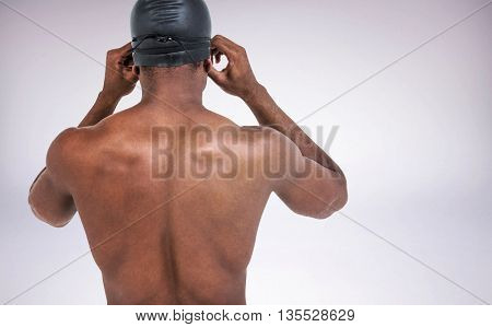 Rear view of swimmer in shirtless wearing swimming goggles against grey background