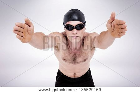 Swimmer preparing to dive against grey background