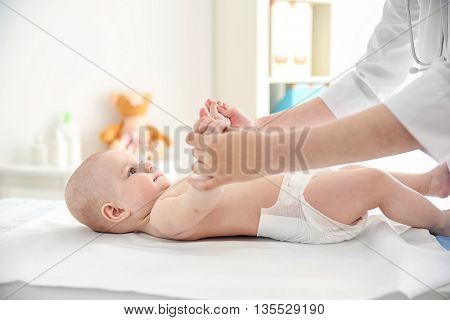 Doctor doing exercises with baby