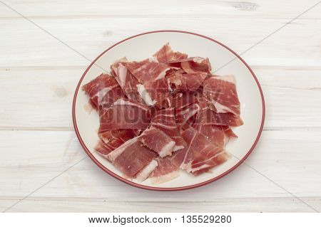 plate with sliced cured ham, on the table