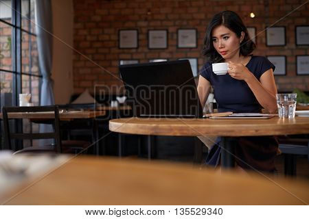 Young businesswoman drinking cofe and checking email in cafe
