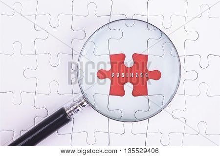 Business Concept - Magnifier Glass on white puzze with Business Word