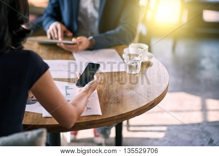 Businesswoman texting message while working over papers