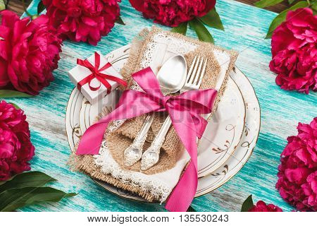 Tableware with crimson peonies and silverware on the light blue background