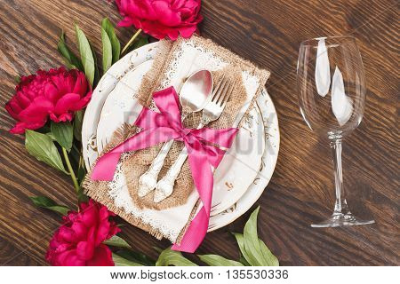 Tableware with crimson peonies and silverware on the wooden background