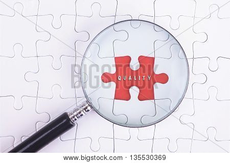 Business Concept - Magnifier Glass on white puzze with QUALITY Word